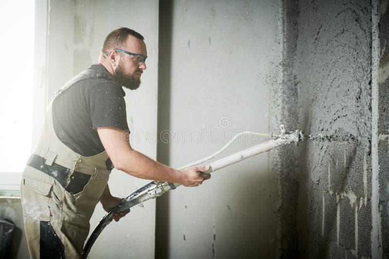 Plasterer using screeder spraying putty plaster mortar on wall. Plasterer using screeder spraying thin-layer putty plaster mortar finishing on brick wall stock photo