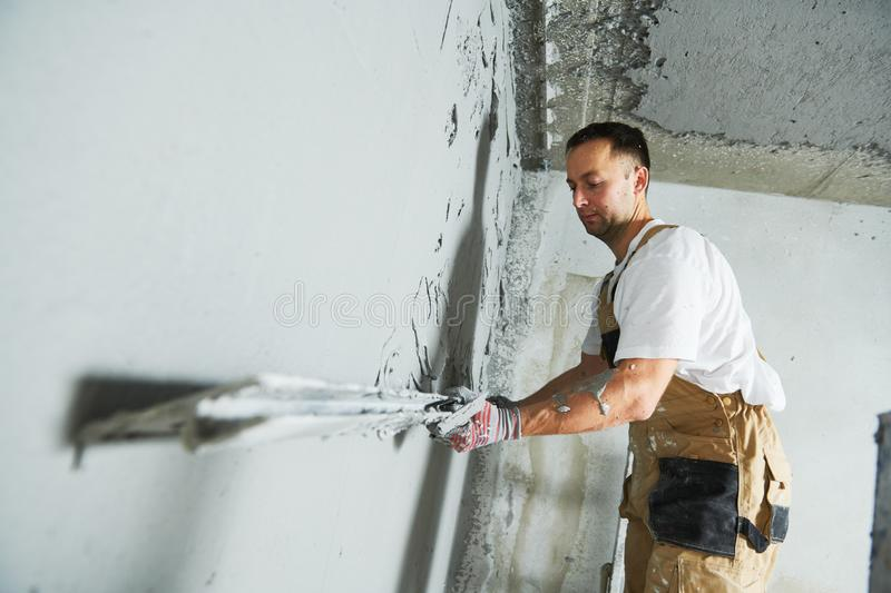 Plasterer using screeder spraying putty plaster mortar on wall. Plasterer using screeder spraying thin-layer putty plaster mortar finishing on brick wall royalty free stock photos
