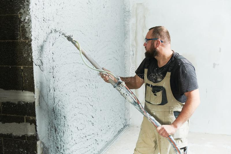 Plasterer using screeder spraying putty plaster mortar on wall. Plasterer using screeder spraying thin-layer putty plaster mortar finishing on brick wall royalty free stock image