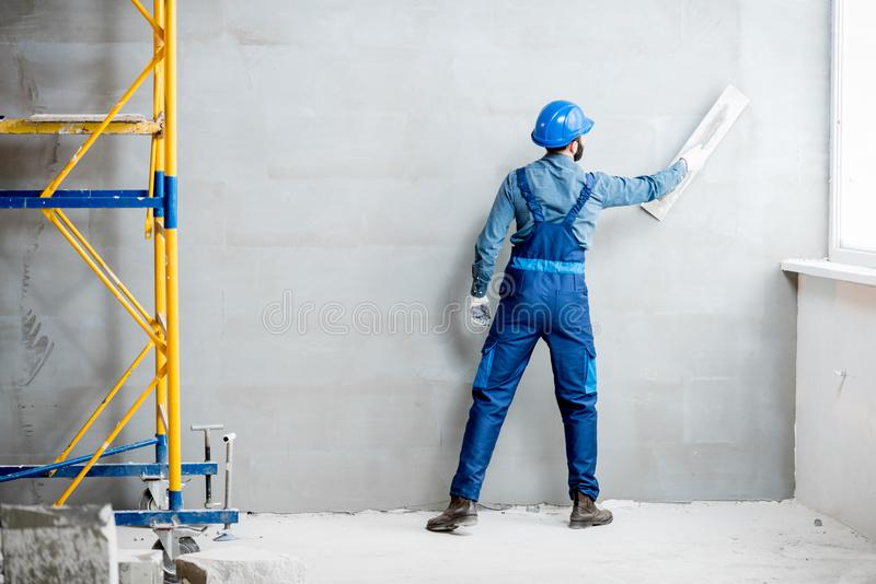 Plasterer working indoors. Plasterer in blue working uniform plastering the wall indoors royalty free stock photos
