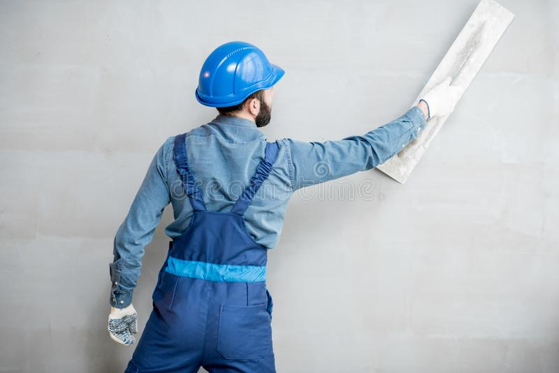 Plasterer working indoors. Plasterer in blue working uniform plastering the wall indoors stock photography