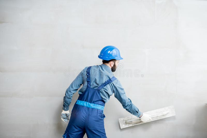 Plasterer working indoors. Plasterer in blue working uniform plastering the wall indoors royalty free stock photo