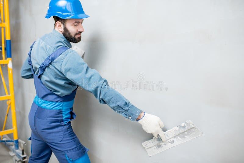 Plasterer working indoors. Plasterer in blue working uniform plastering the wall indoors stock images