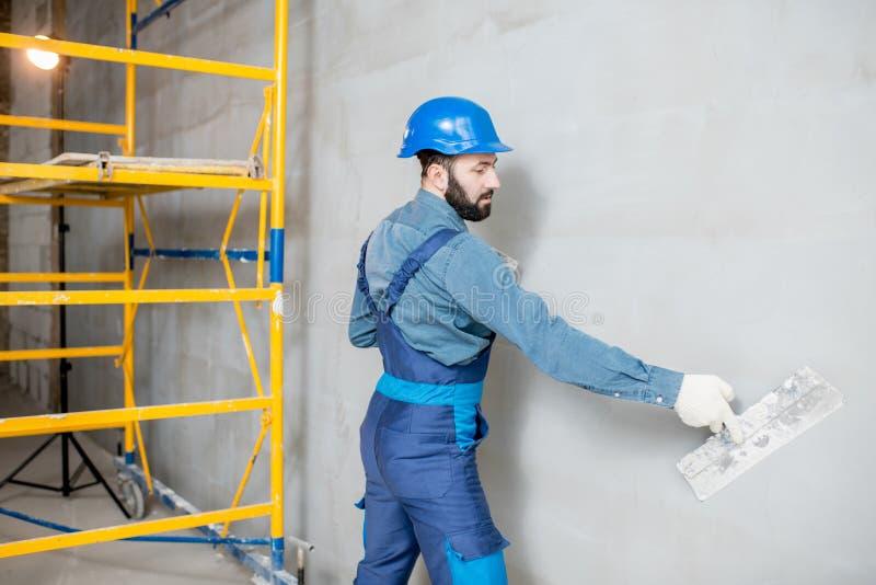 Plasterer working indoors. Plasterer in blue working uniform plastering the wall indoors stock image