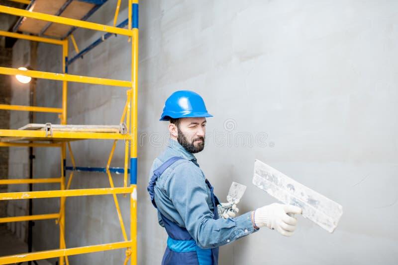Plasterer working indoors. Plasterer in blue working uniform plastering the wall indoors stock photo