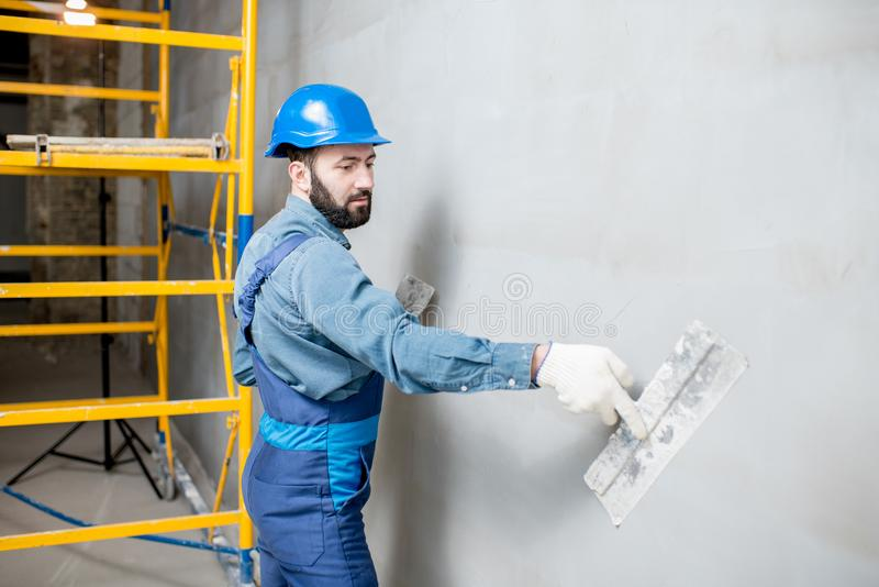 Plasterer working indoors. Plasterer in blue working uniform plastering the wall indoors royalty free stock photography