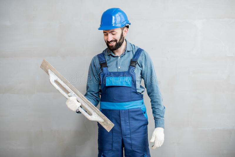 Plasterer working indoors. Portrait of a handsome builder in blue working uniform plastering the wall indoors royalty free stock photography