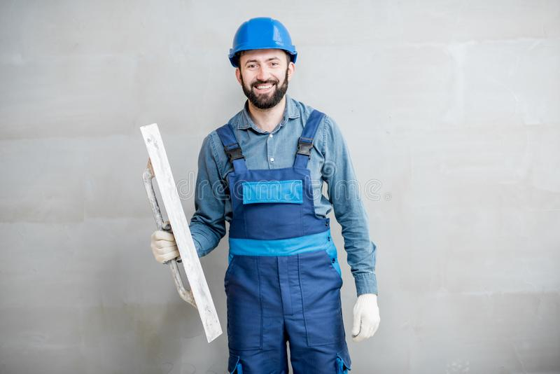Plasterer working indoors. Portrait of a handsome builder in blue working uniform plastering the wall indoors stock images