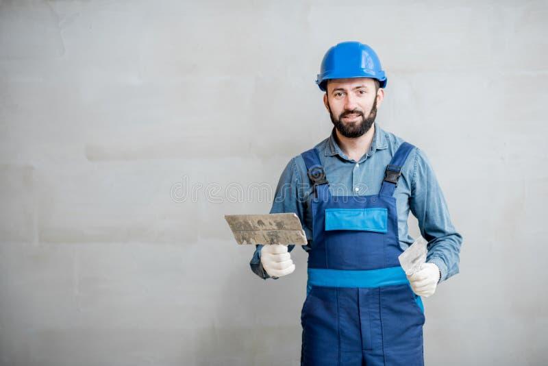 Plasterer working indoors. Portrait of a handsome builder in blue working uniform plastering the wall indoors stock image