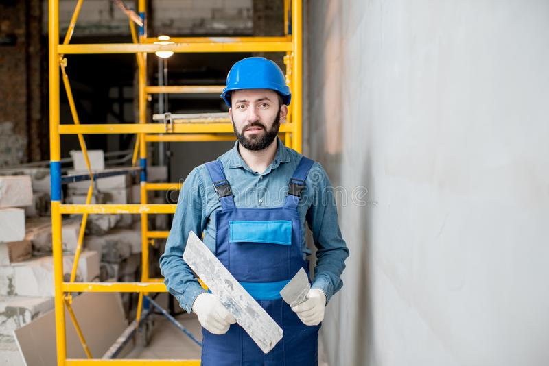 Plasterer working indoors. Portrait of a handsome builder in blue working uniform plastering the wall indoors royalty free stock photo