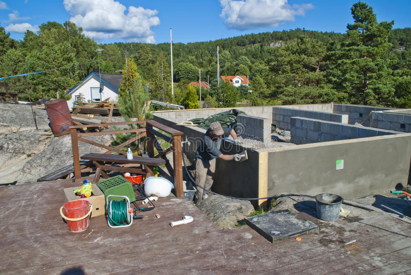 Plastering foundation. Here have my sons and I bricked up a foundation to a cabin by the iddefjord in halden, picture shows my youngest son in full swing to royalty free stock photos