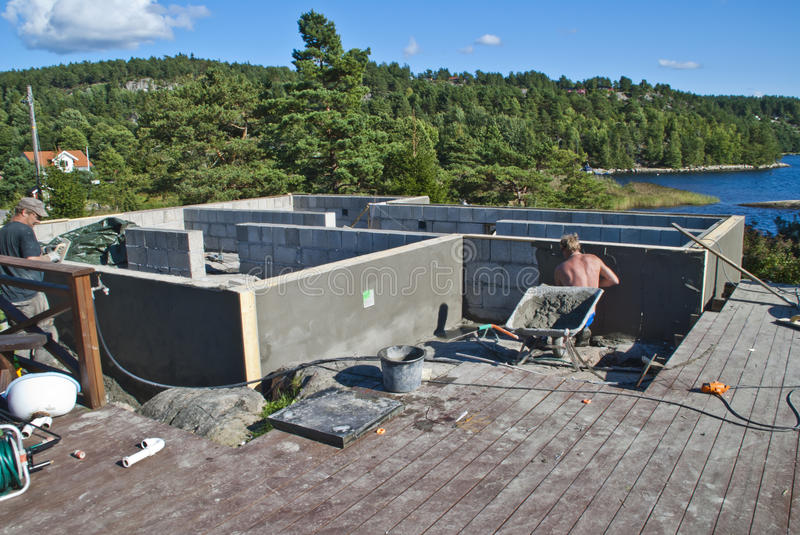 Plastering foundation. Here have my sons and I bricked up a foundation to a cabin by the iddefjord in halden, picture shows my sons in full swing to plastering royalty free stock image