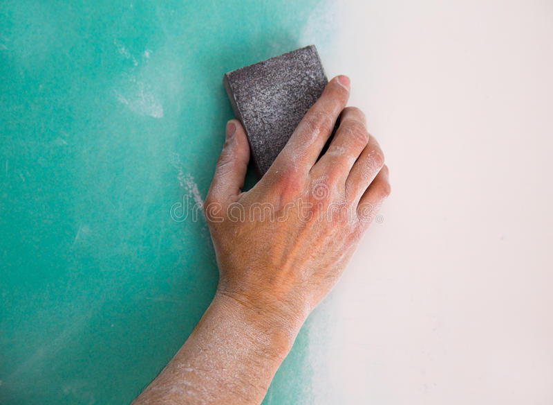 Plastering man hand sanding the plaste in drywall seam royalty free stock image