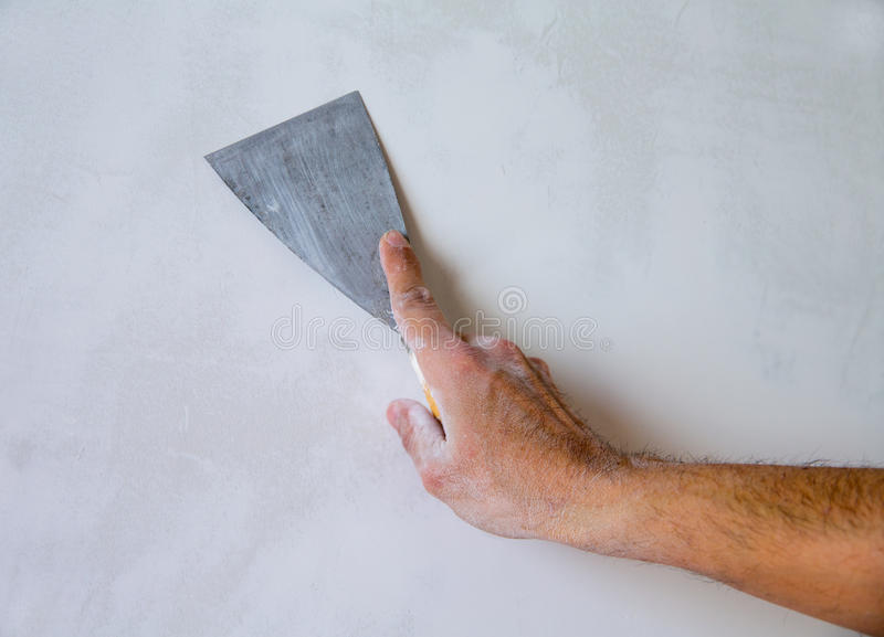 Plastering wall with plaste and plaster spatula trowel. Plastering man hand with plaste and plaster spatula trowel in wall royalty free stock image