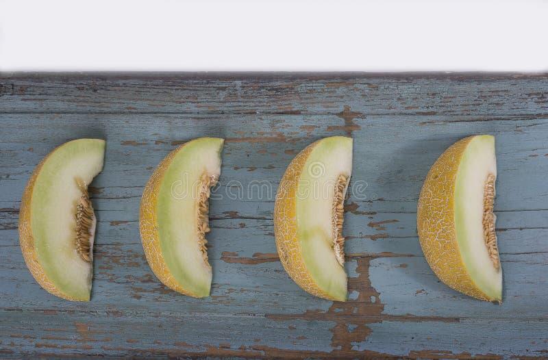 Plasterki świeży żółty melon lub kantalup na olg grungy wo obrazy stock