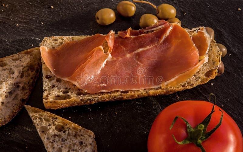 Plasterki świeży domowej roboty Alpejski Baguette z jamon, oliwki i obrazy royalty free