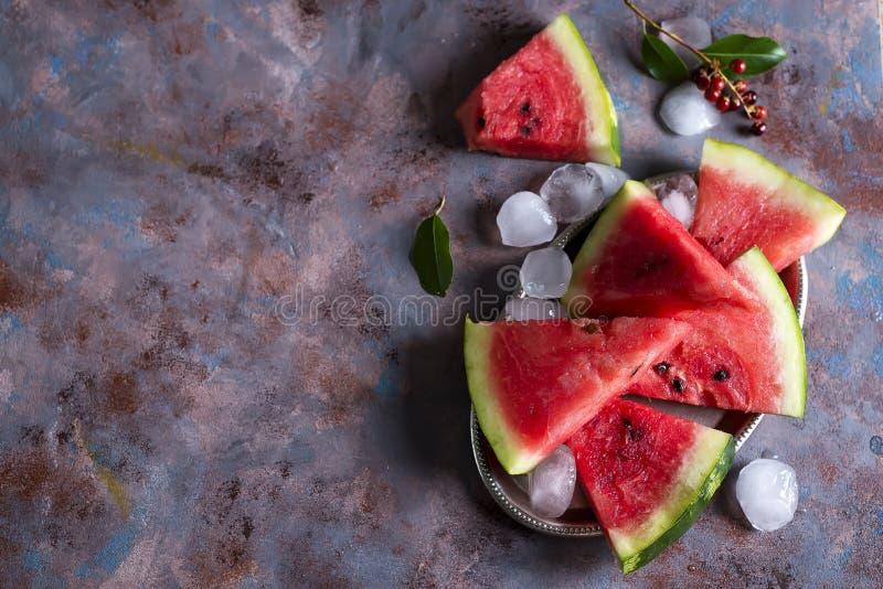 Plasterki arbuz na odprasowywają talerza z lodem fotografia stock