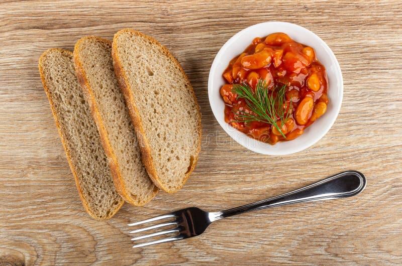Plasterki chleb, fasole z warzywami i pomidorowy kumberland, koper w pucharze, rozwidlenie na stole Odg?rny widok zdjęcie stock