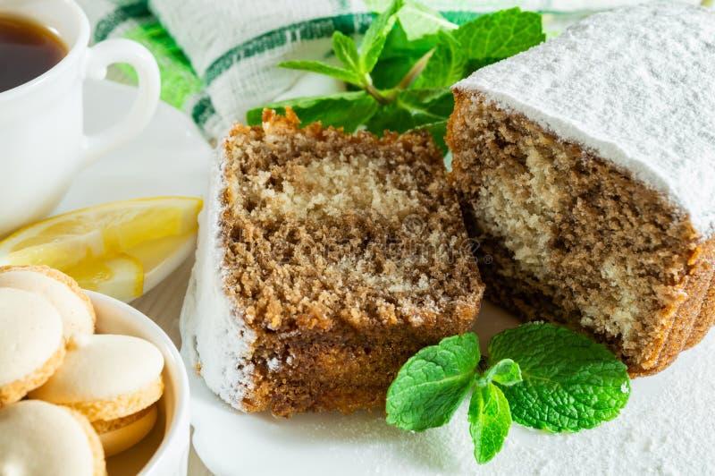Plasterki ciastko tort, Ñ  w górę herbaty z cytryną, mali ciastka i nowi liście na białym drewnianym stole, zdjęcia stock
