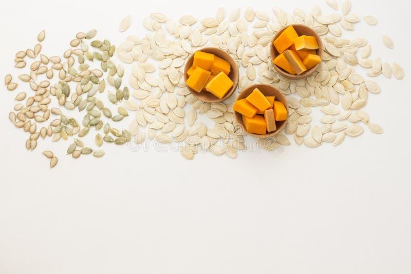 Plasterki dyni pocięte w miski drewniane i nasiona na białym tle Wyświetl od powyżej Istnieje miejsce na tekst zdjęcie royalty free