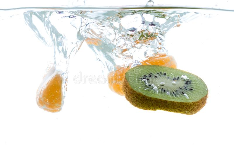 Plasterki kiwi i mandarynka rzucający w wodę Widok spod wody zdjęcie royalty free