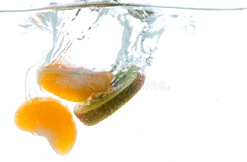 Plasterki kiwi i mandarynka rzucający w wodę Widok spod wody fotografia stock