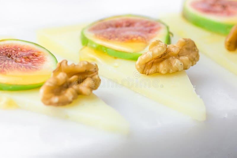 Plasterki leczący półtwardy Hiszpański koźli ser z orzechami włoskimi, dojrzałe figi mżyli z miodem na bielu marmuru porci desce  zdjęcia royalty free