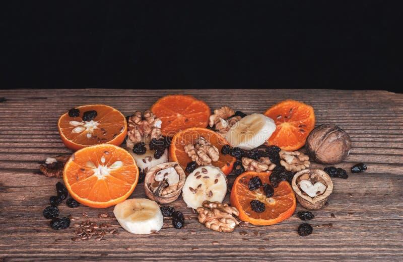 Plasterki mandaryny i banany z dokrętkami i rodzynkami na Nieociosanej Drewnianej desce zdjęcie stock