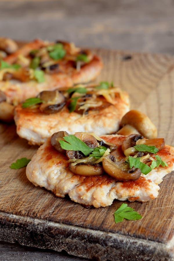 Plasterki piec indyczy mięso Smażący Indyczy stki z serem i pieczarkami na ciapanie desce i starym drewnianym stole zdjęcie stock