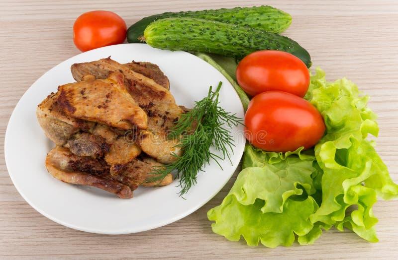 Plasterki pieczona wieprzowina w szklanym talerzu, pomidory, ogórek obraz royalty free