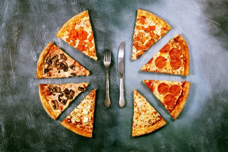 Plasterki pizza z różnymi plombowaniami na ciemnym textured tle fotografia stock