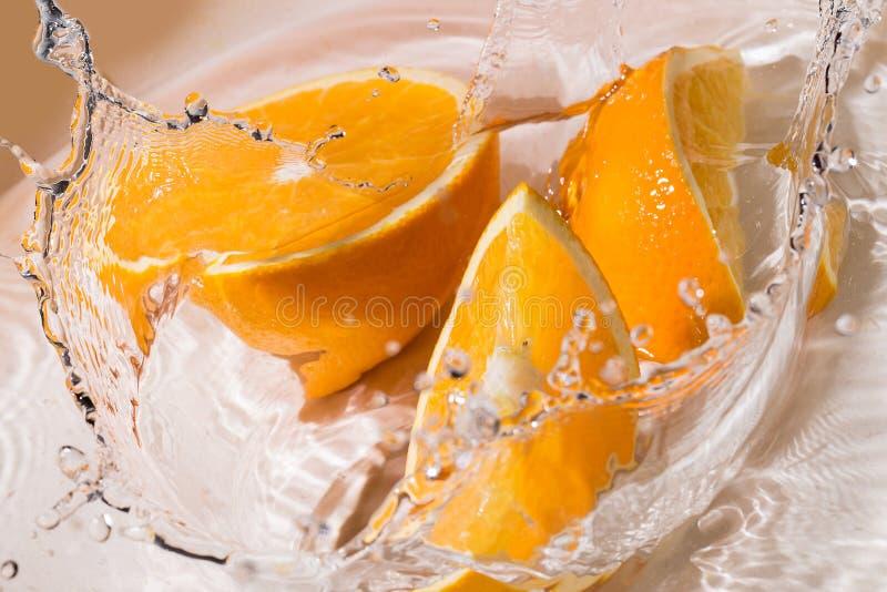 Plasterki pomarańcze w wodzie obraz stock