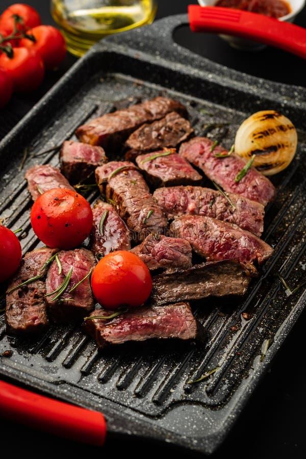 Plasterki soczysty stek z czereśniowymi pomidorami na grill niecce fotografia stock