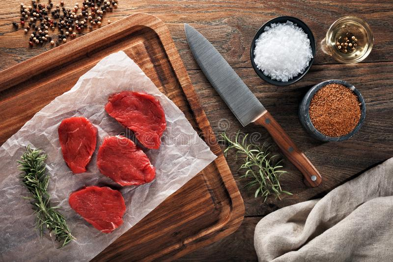 Plasterki surowy łydkowy mięso na białym kucharstwo papierowym i drewnianym rozcięcie stole obrazy stock