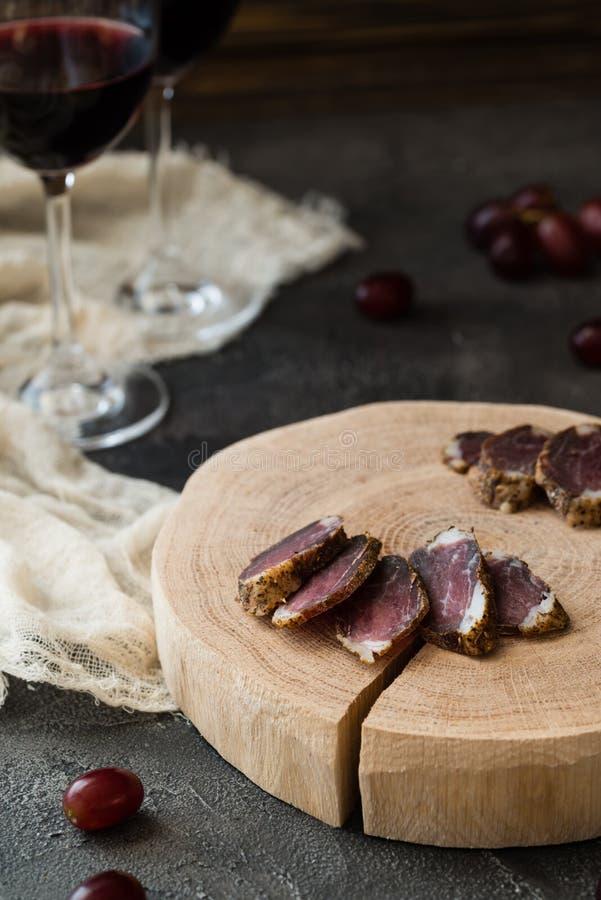 Plasterki wysuszony mięso na drewnianym cięciu, czerwonych winogronach i dwa szkłach czerwone wino, obraz stock