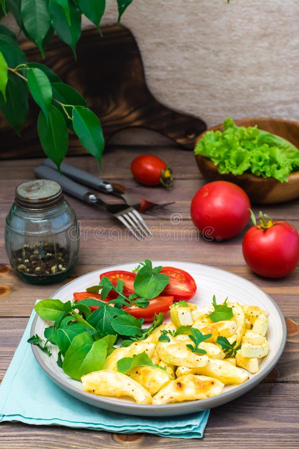 Plasterki zucchini piec w pikantność z serem na talerzu z pomidorami i arugula na drewnianym stole zdjęcie royalty free