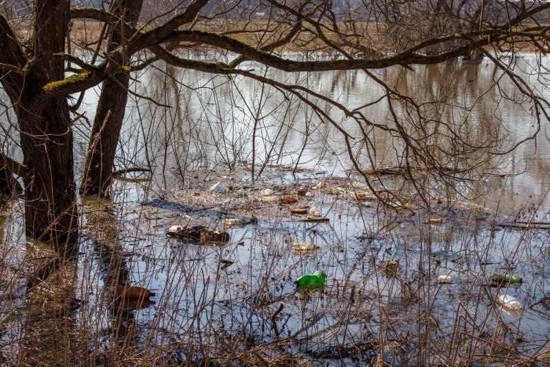 Plastic afval op de rivierbank die tijdens de de lentevloed drijven royalty-vrije stock foto's