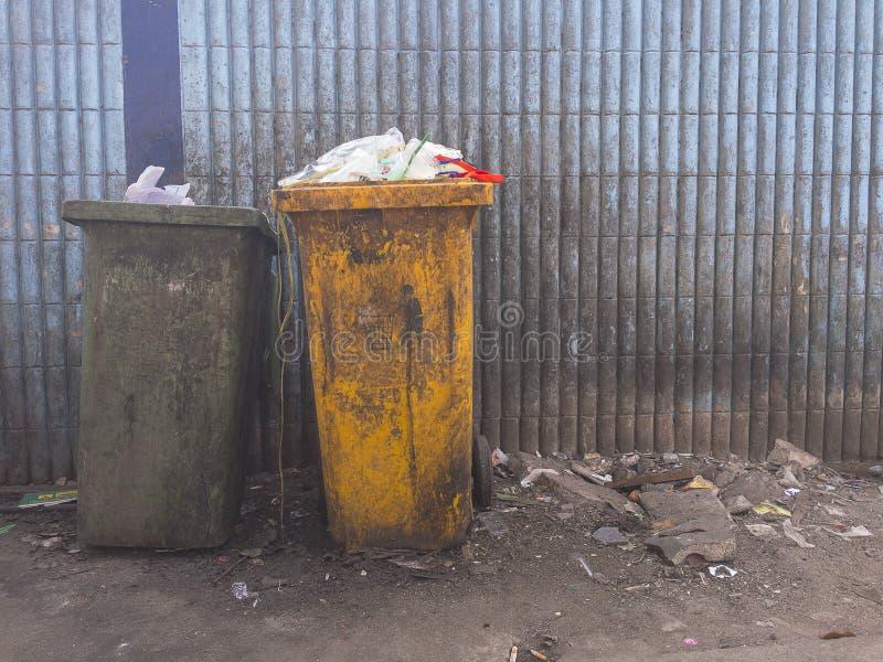 Plastic afvalhoogtepunt van vuile groen van de huisvuilbak en geel op vuile lichtblauw van muur royalty-vrije stock foto's
