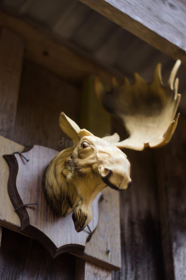 Plastic Amerikaanse elandenhoofd buiten opgezet in een eenvoudige plankmuur De Amerikaanse eland mist een hoorn en glimlacht stock fotografie