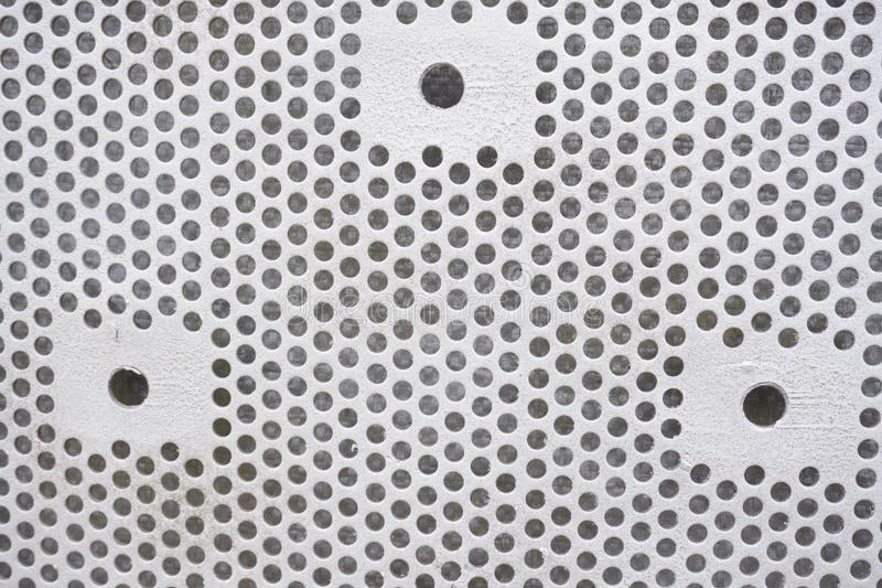 Plastic background with circles, white tone, great for design. Texture with perforation of round holes. White plate with dots. royalty free stock photography