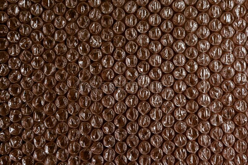 Plastic background texture cellophane wrapping packing wrap packet bead ball color maroon bordo brown chocolate. Cellophane and plastic background. The texture royalty free stock images