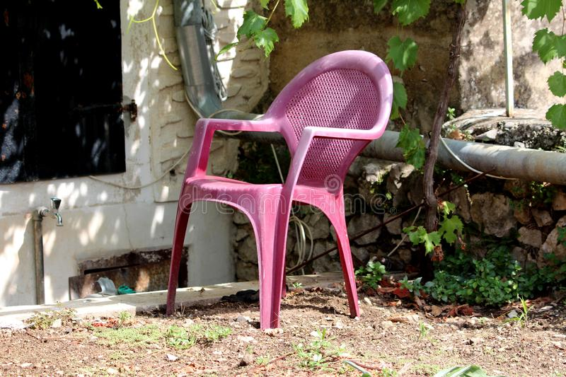 Plastic backyard chair with faded dark pink color surrounded with traditional stone wall and gutter pipe in front of family house stock photo