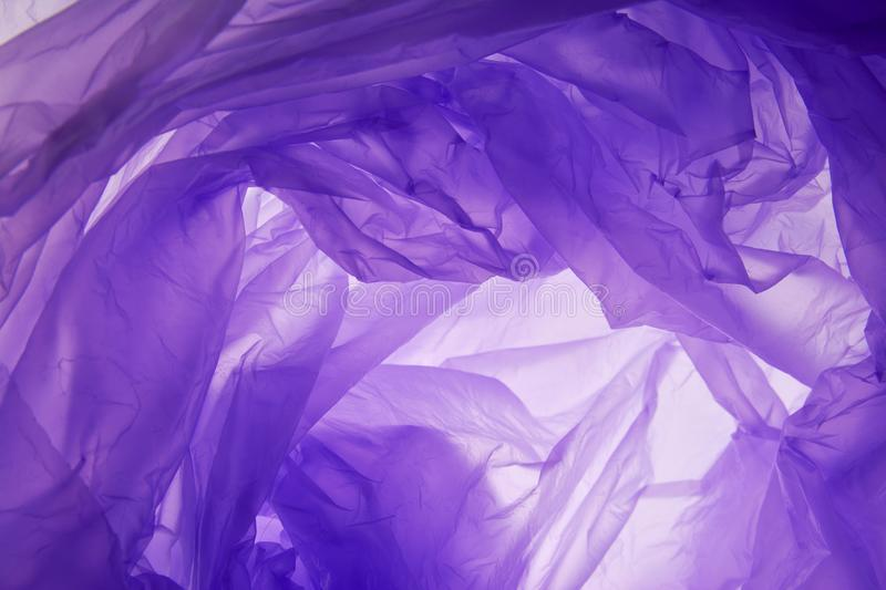 Plastic bag background. Modern artificial synthetic lilac color wrinkled relief. Wavy rough crumpled whirl wrapping trendy. Structure. Close up top detail macro stock images
