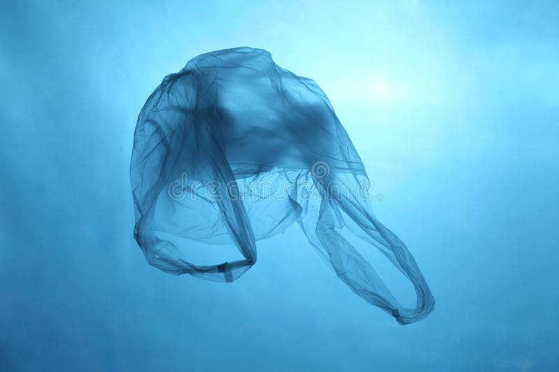 Plastic bag in blue water, garbage under water, plastic pollution of the oceans stock photography