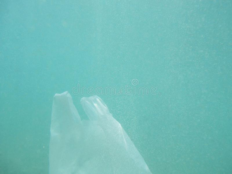Plastic bag floating into the sea. Polluted enviromental. Recycle. Garbage stock photo