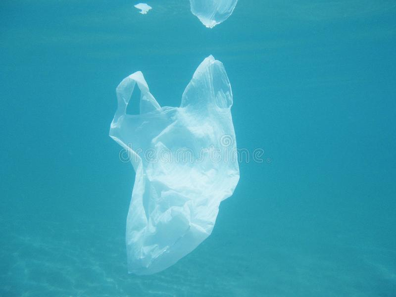 Plastic bag floating into the sea. Polluted environmental. Recycle. Garbage stock photo