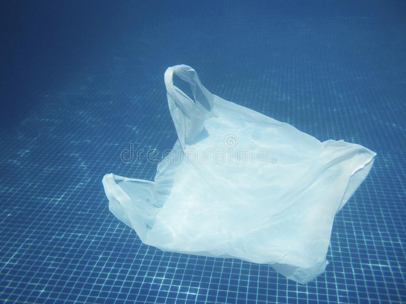 Plastic bag floating into the water. Polluted enviromental. Recycle. Garbage royalty free stock photos