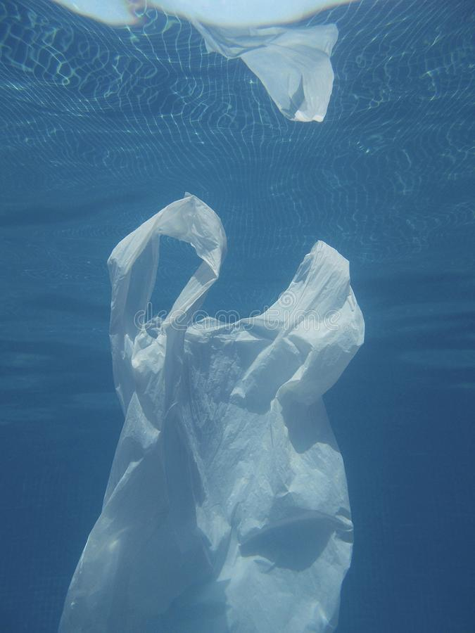Plastic bag floating into the water. Polluted enviromental. Recycle. Garbage stock images
