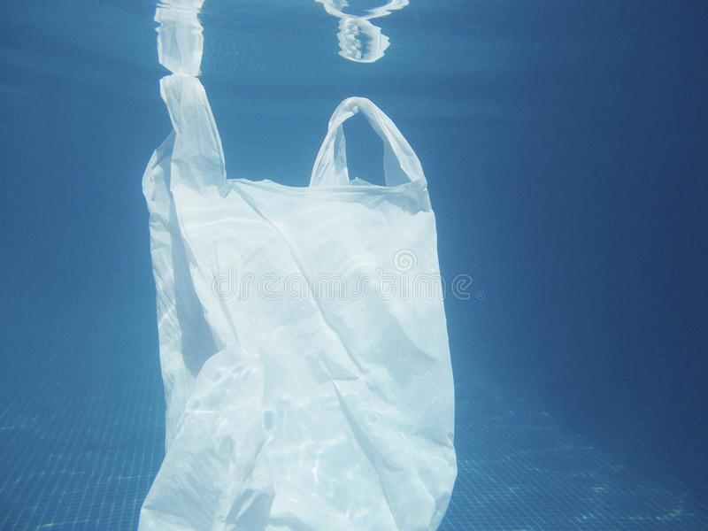 Plastic bag floating into the water. Polluted enviromental. Recycle. Garbage stock photo