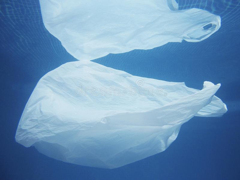 Plastic bag floating into the water. Polluted enviromental. Recycle. Garbage stock image